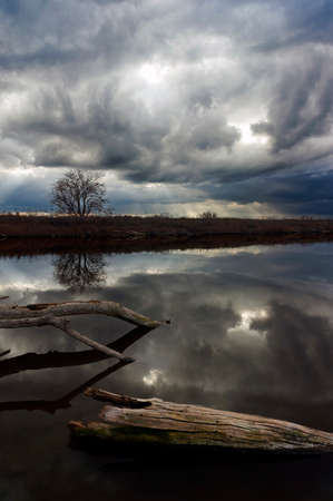 Reflection of rolling thunderstorm, wild weather, and rays of sunshine, over wildlife refuge, San Joaquin Valley, California
