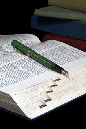 Old books, open dictionary, and fountain pen  Stock Photo