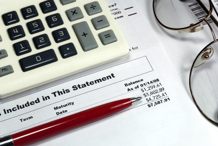 Statement of account, vintage pen, vintage calculator, vintage eye glasses, closeup desktop view
