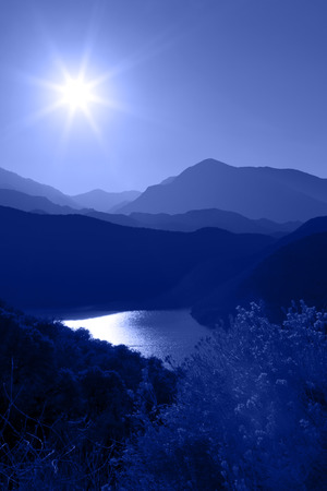 Several layers of mountain ranges stacked in blue silhouette, sun, lake, rabbit brush in foreground