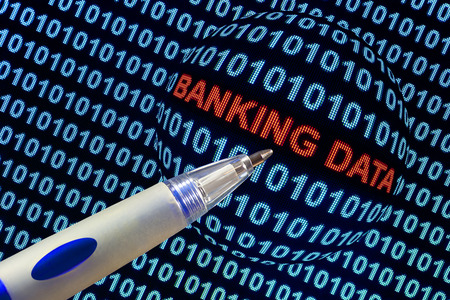 Digital binary code on computer screen, pen pointing out  banking data  in red characters  Stock Photo