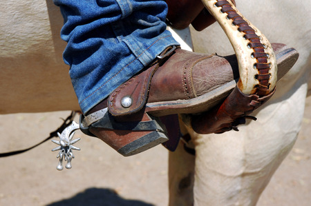 cowboy on horse: Western boot with old time spurs in stirrup. Stock Photo