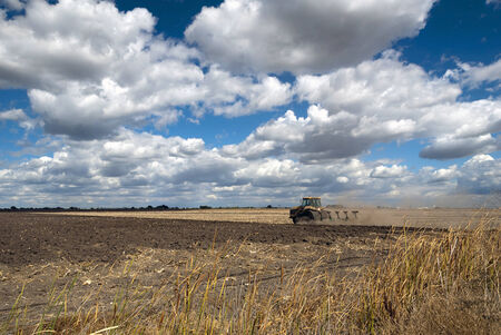 Tractor plowing field, deep blue sky, Summer clouds, San Joaquin Valley, California.