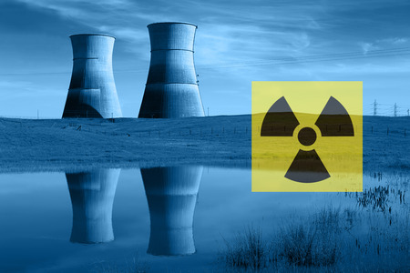 radiation hazard: Nuclear reactor cooling towers in blue, reflected in pond, and international nuclear radiation hazard symbol. Stock Photo