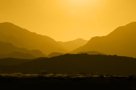 Several layers of mountain ranges stacked in yellow silhouette. Stock Photo
