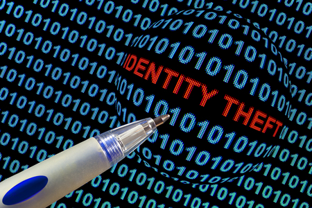 stolen identity: The words identity theft in red binary code on computer monitor. Stock Photo