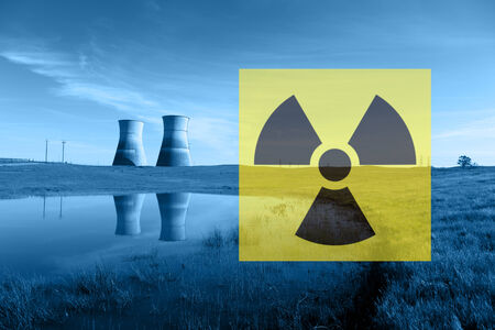Nuclear reactor cooling towers in blue, reflected in pond, and international nuclear radiation hazard symbol. Banco de Imagens