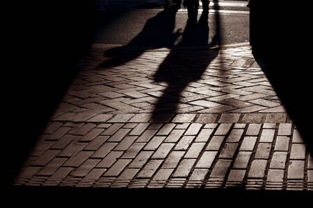 Silhouetted shadows of people walking on brick pavement, strongly backlit, stylized.