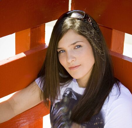 Girl leaning against red fence Stock Photo