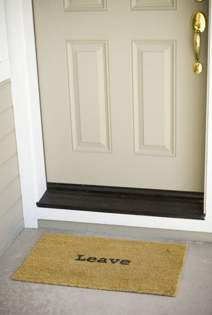 A mat in front of a door that simply states,