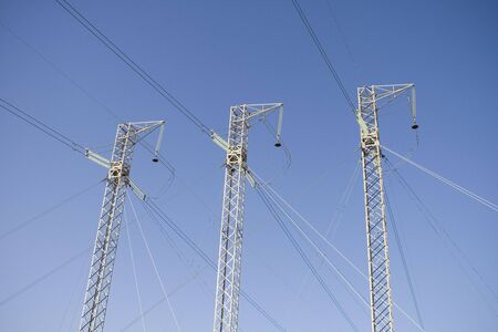 Power Lines Against Blue Sky Stock Photo