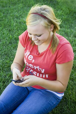 Girl sitting on the grass with a cell phone in hand, smiling at a text message.