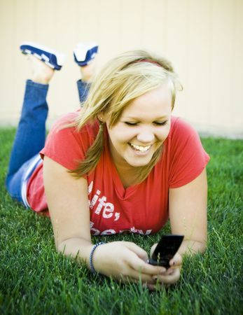 Girl laying on her stomach on the grass with a cell phone in hand, smiling at a text message. Image is created using a golden hue and soft focus.