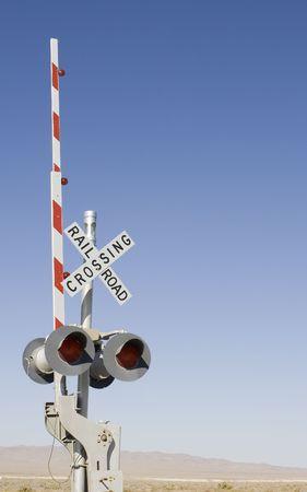 Spoorwegovergang bord in de woestijn met veel blauwe lucht voor de kopie aan de rechterkant.