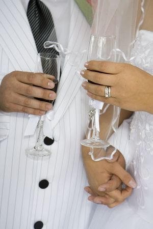 Torsos of a bride and groom with brides ring visible sharing a toast. Stock Photo