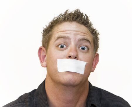 Early 20s man mug shot with wide eyes and a piece of tape over his mouth. White background. Stock Photo