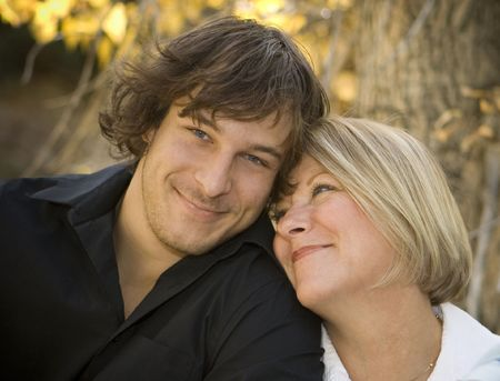 Portrait of a mother and her son. Mom is looking at her son, hes smiling at the camera.