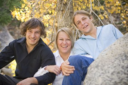 Foto van een enkele moeder met haar twee tienerjongens. Warme tinten met vallen achtergrond.