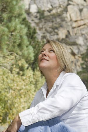 Healthy mature woman in an outdoor setting looking up at the sky. Stock Photo