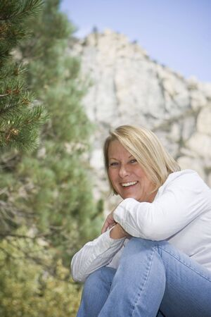 Healthy mature woman in an outdoor setting with an evergreen tree and rockmountain behind her.