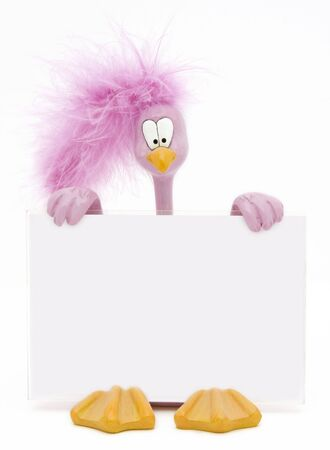 Pink ceramic cartoon-style bird with a fluffy feather on his head holding a blank sign. Stock Photo