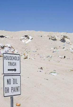 A Nevada landfill with garbage and blue sky. Household Trash and No Oil or Paint sign visible. Stock Photo