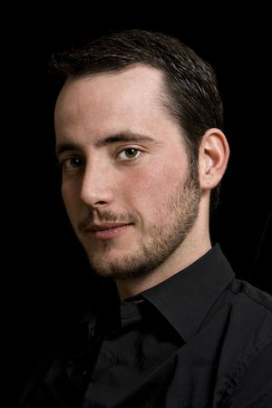 College-age man with one side of his face in shadow (black reflector used). Black shirt and background.
