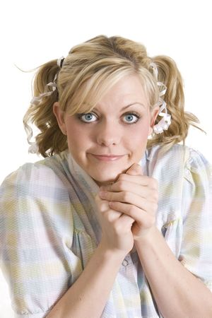 imploring: Funny image of a blonde girl with big blue eyes dressed as a little girl and clasping her hands.