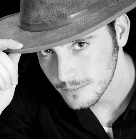 College-age man with tipping his hat. Black background and focus on his eyes.