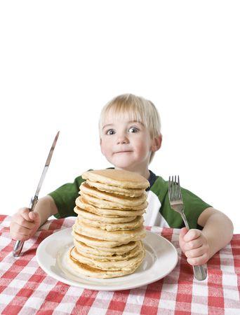 Jongetje met een grote plaat van pannenkoeken, een mes en vork op tafel doek. Ondiepe DOF met de nadruk op de pannenkoeken.
