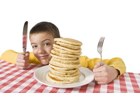 Jongen met een grote plaat van pannenkoeken, een mes en vork op tafel doek. Ondiepe DOF met de nadruk op de pannenkoeken.