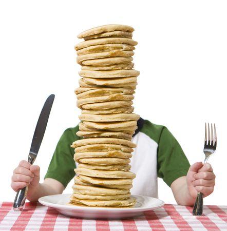 Jongetje verborgen achter een grote plaat van pannenkoeken, met een mes en vork zichtbaar op een tafel doek.