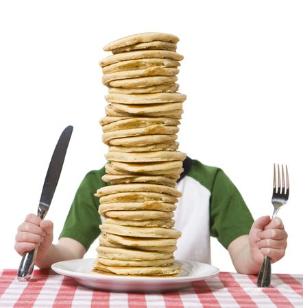 flapjacks: Little boy hidden behind  a giant plate of pancakes, with a knife and fork visible on a table cloth.  Stock Photo