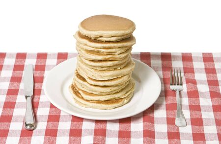 Giant plate of pancakes, a knife and fork on a table cloth.  Stock Photo - 4209274