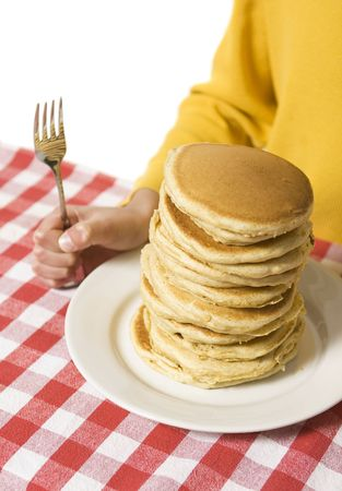 Giant plate of pancakes, with a hand holding a fork against a red checkered tablecloth.