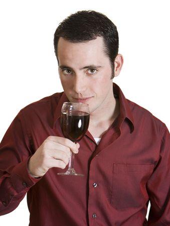 Jong donkerharig man met rood shirt en glas rode wijn geïsoleerd op witte achtergrond. Stockfoto