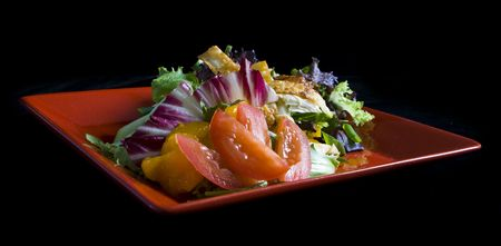 Gourmet chicken salad on red plate with black background