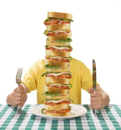 Giant sandwich on a white plate, with hands holding a a knife and fork on a table cloth.  Zdjęcie Seryjne