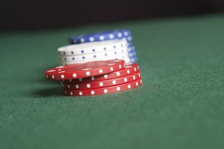 Red, white and blue poker chips on a green felt surface. Stock Photo