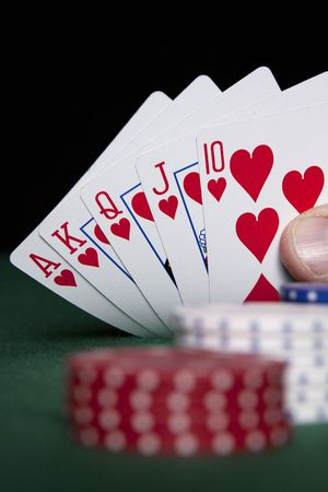Royal Flush in focus with red, white and blue poker chips on a green felt surface. Stock Photo - 5995235