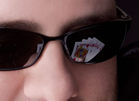 Close-up of mans glasses with a royal flush reflected in them.