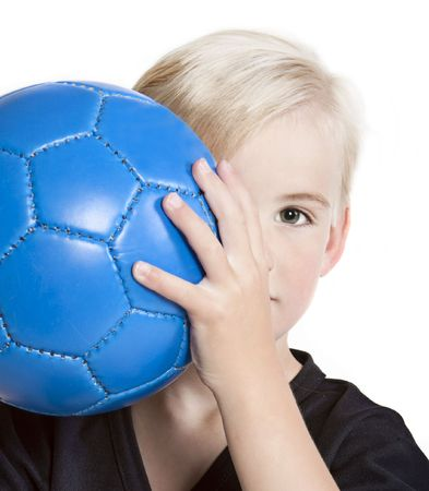 Young (preschool age) boy with blue soccer ball partially hidden behind face.