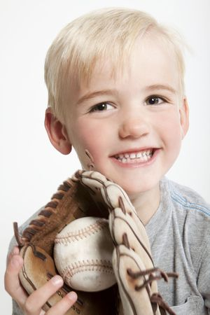 Young (preschool age) boy with a baseball in his glove and a big smile. Stock Photo