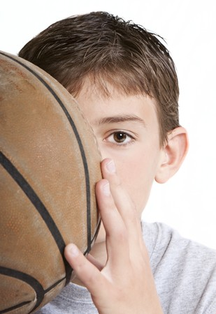 Youth with basketball partially hidden behind face. Stock Photo