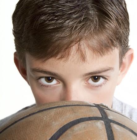 Jonge tiener peering over de bovenkant van een basket bal. Op wit wordt geïsoleerd.