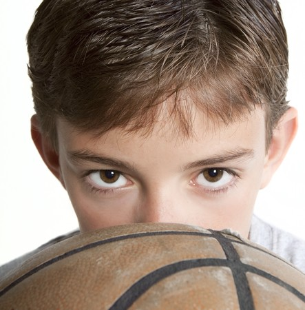Young teen peering over the top of a basketball. Isolated on white.