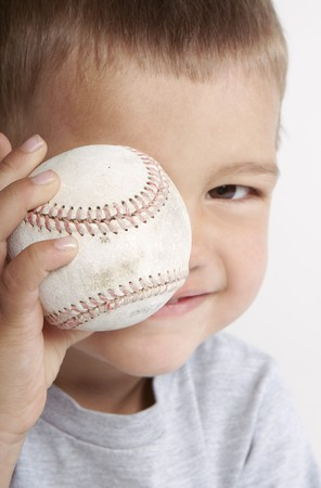 Toddler holding baseball up to his eye. Main focus on the baseball. Stock Photo