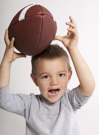 Cute toddler boy catching football with happy expression. Stock Photo