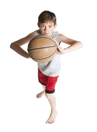 Jonge tiener Dim basket bal. Op wit wordt geïsoleerd.  Stockfoto