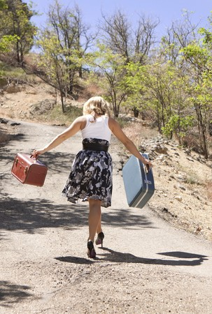 Girl walking down road carrying suitcases.